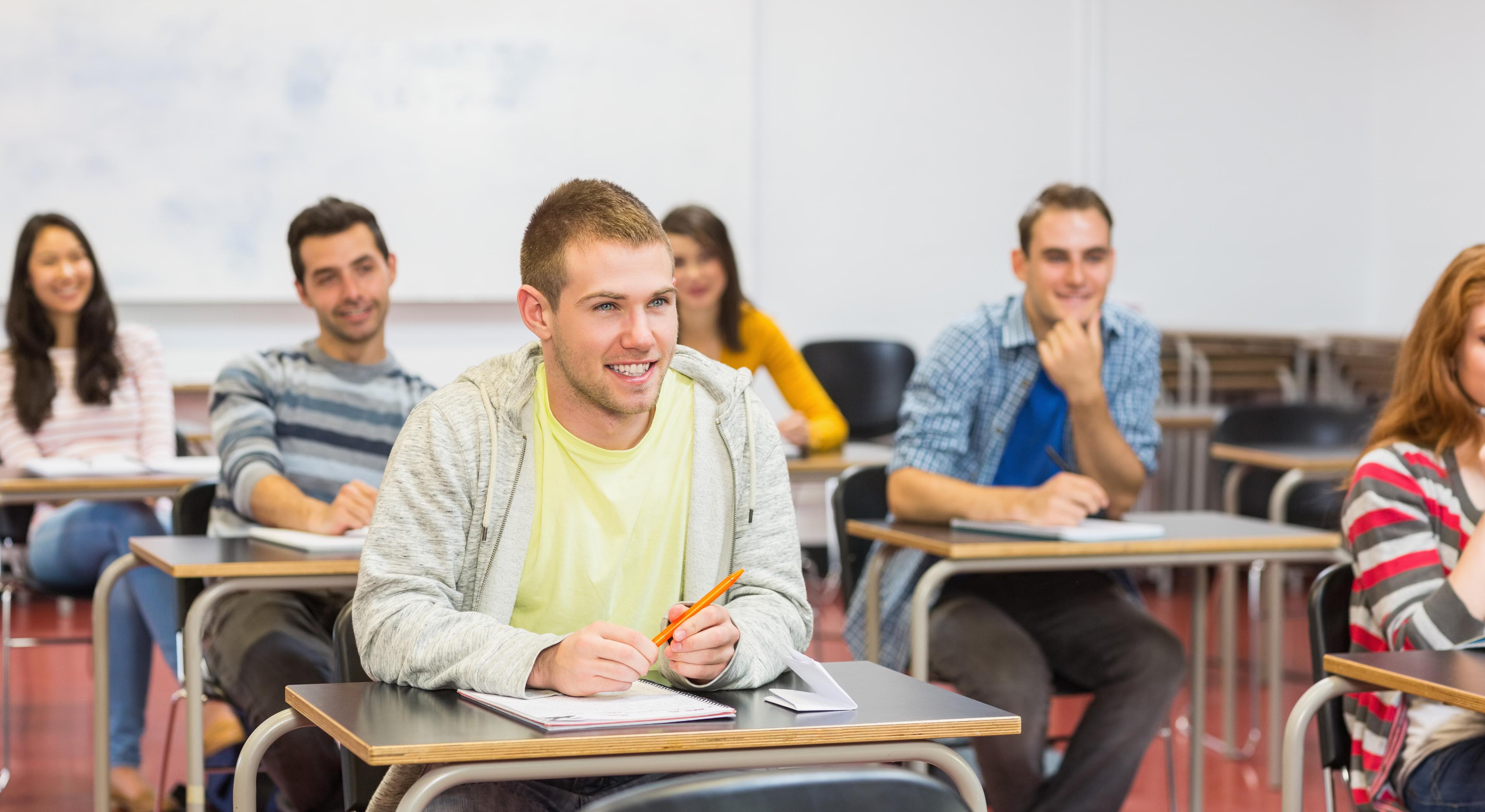 Group of young students smiling in the college classroom